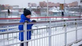 Jungenjugendlicher im Blau hinunter Jacke verlor in der Stadt Er ist am Bahnhof und unten schaut stock video