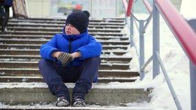 Jungenjugendlicher im Blau hinunter Jacke verlor in der Stadt Er sitzt auf einem kalten Treppenhaus, schaut herum stock video