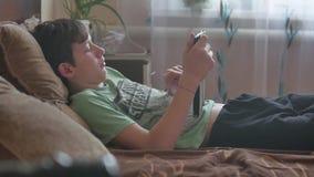 Jungenjugendlicher liegt mit Tablettensocial media Jungenjugendlicher, der zuhause Spiel auf einer Tablette auf dem Bett spielt stock video footage