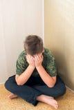 Jungenjugendlicher mit der Krise, die in der Ecke des Raumes sitzt stockbild