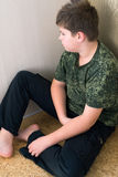 Jungenjugendlicher mit der Krise, die in der Ecke des Raumes sitzt Stockfotos