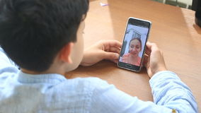 Jungenjugendlichgriffe ein Videochat mit einer Frau auf einem Smartphone stock video footage