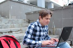 Jungenjugendlichschüler oder -student sitzt auf der Treppe und arbeitet im Computer, tragende Gläser, in einem Hemd und lächelt,  stockbild