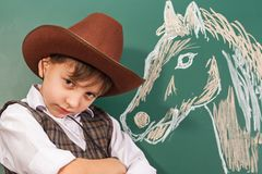 Jungenkünstlercowboy mit einem Pferd gezeichnet von ihm stockfotografie