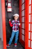 Jungenkappe, die in einer roten Telefonzelle steht Stockbild