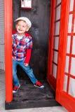 Jungenkappe, die in einer roten Telefonzelle steht Stockbilder