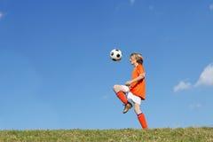 Jungenkind, das Fußball oder Fußball spielt Lizenzfreie Stockfotografie