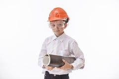 Jungenkind in einem Schutzhelm und Schutzbrillen mit einem Bau Stockbild