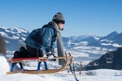 Jungenkind im Winter auf Schlitten Stockbilder