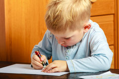 Jungenkind mit dem Stiftschreiben, das Hausarbeit tut Zu Hause Stockfotos