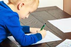 Jungenkind mit dem Stiftschreiben, das Hausarbeit tut Zu Hause Lizenzfreies Stockbild