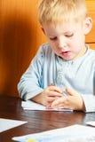 Jungenkind mit dem Stiftschreiben, das Hausarbeit tut Zu Hause Stockfoto