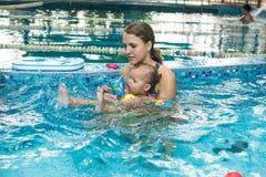 Jungenkinderkind acht Jahre alte Spritzen im Swimmingpool, der offene Arme der Spaßfreizeitbetätigung hat Lizenzfreie Stockbilder