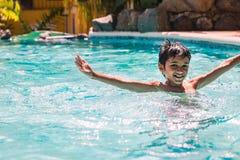 Jungenkinderkind acht Jahre alte Spritzen im Swimmingpool, der Spaßfreizeitbetätigung hat Stockfotografie