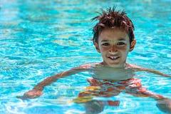 Jungenkinderkind acht Jahre heller Tag des alten inneren Spaßes des Swimmingpool-Porträts glücklichen Lizenzfreie Stockfotos
