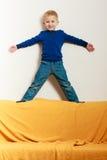 Jungenkinderkindervorschüler, der auf Rückenlehne des Sofainnenraums steht Lizenzfreie Stockbilder