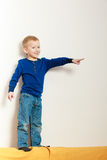 Jungenkinderkindervorschüler, der auf Rückenlehne des Sofainnenraums steht Lizenzfreie Stockfotos