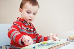 Jungenkleinkindzeichnung mit Farbe zeichnet Markierungen auf Papier im Album an Lizenzfreies Stockbild