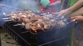 Jungenkochfleisch auf dem Grill stock video