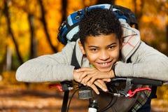 Jungenlächeln, das auf Fahrradheck legt Stockbilder