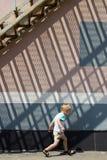 Jungenlack-läufer unter den Treppen stockbild