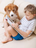 Jungenlesung für seinen Hund zu Hause Lizenzfreies Stockfoto