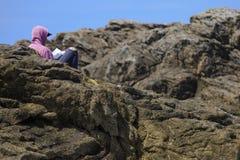 Jungenlesung zwischen den Felsen lizenzfreie stockfotos