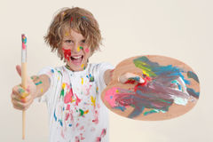 Jungenmalerei mit Bürste und pallete Stockfotos