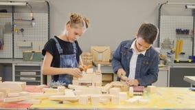 Jungenmeister in der Werkstatt Wenig Erbauerkonzept Kinder, die in der Zimmerei arbeiten Junge, der Nagel in der hölzernen Planke stock footage
