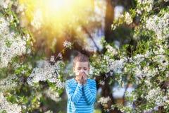 Jungenniesen im Park vor dem hintergrund eines blühenden Baums, weil er allergisch ist lizenzfreie stockbilder