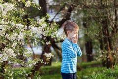 Jungenniesen im Park vor dem hintergrund eines blühenden Baums, weil er allergisch ist stockbilder