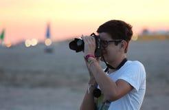 Jungenphotograph in einem Strand der Sonnenuntergang auf dem Meer Stockfotos