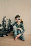 Jungenpirat mit einem Papageien und einem Segelboot Lizenzfreie Stockfotografie