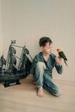 Jungenpirat mit einem Papageien und einem Segelboot Stockbild