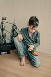 Jungenpirat mit einem Papageien und einem Segelboot Lizenzfreies Stockfoto