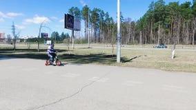 Jungenradfahrer im Verkehr auf der Stadtfahrbahn gesamtlänge Konzept der Gefahr auf den Straßen stock footage
