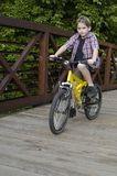 Jungenreitfahrrad auf Brücke Lizenzfreies Stockbild