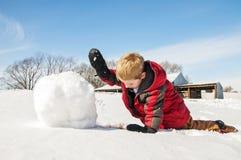 Jungenrollenschnee für Schneemann Stockfoto