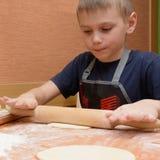 Jungenrollenteig mit einem großen hölzernen Nudelholz, wie er die Kuchen vorbereitet Lizenzfreie Stockbilder