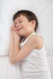 Jungenschlaf im weißen Bett Stockbilder