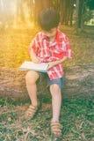 Jungenschreiben auf Buch getrennte alte Bücher Abbildung der roten Lilie Lizenzfreie Stockfotos