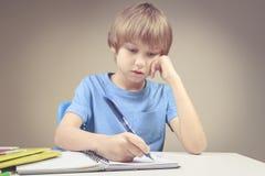 Jungenschreiben auf Papiernotizbuch Junge, der seine Hausarbeitübungen tut Lizenzfreie Stockbilder