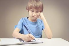 Jungenschreiben auf Papiernotizbuch Junge, der seine Hausarbeitübungen tut Lizenzfreie Stockfotografie