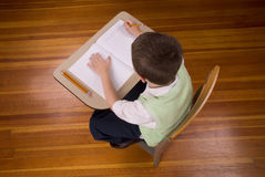 Jungenschreiben am Schuleschreibtisch Stockfotos