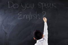 Jungenschreibenstext sprechen Sie Englisch lizenzfreie stockfotografie