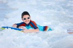 Jungenschwimmen auf Boogiebrett Stockfotos