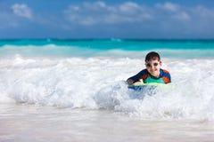 Jungenschwimmen auf Boogiebrett Stockbild