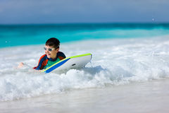 Jungenschwimmen auf Boogiebrett Lizenzfreie Stockfotos