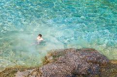Jungenschwimmen im haarscharfen Türkiswasser Stockfotos