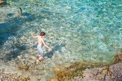Jungenschwimmen im haarscharfen Türkiswasser Lizenzfreie Stockfotografie